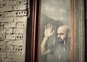 Man looking outside window during isolation or quarantine